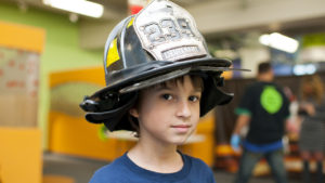 Child wearing fireman's hat